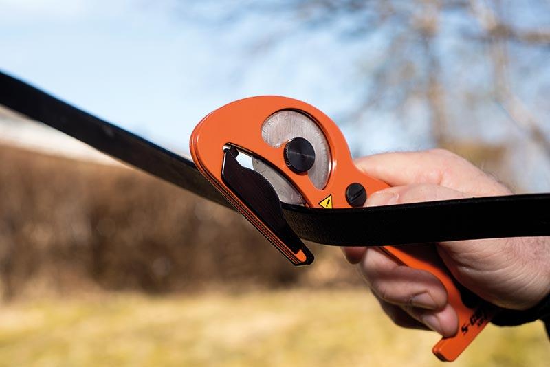 Bild på en orange S-CUT XC-E som skär igenom en läderrem.