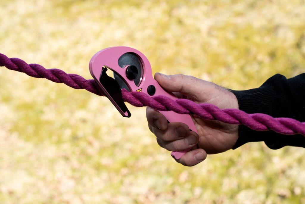 Bild på en rosa S-CUT XC-E som är på väg att kapa ett lila grimskaft. S-CUT är designad för hästens säkerhet, hur säker är DIN häst?