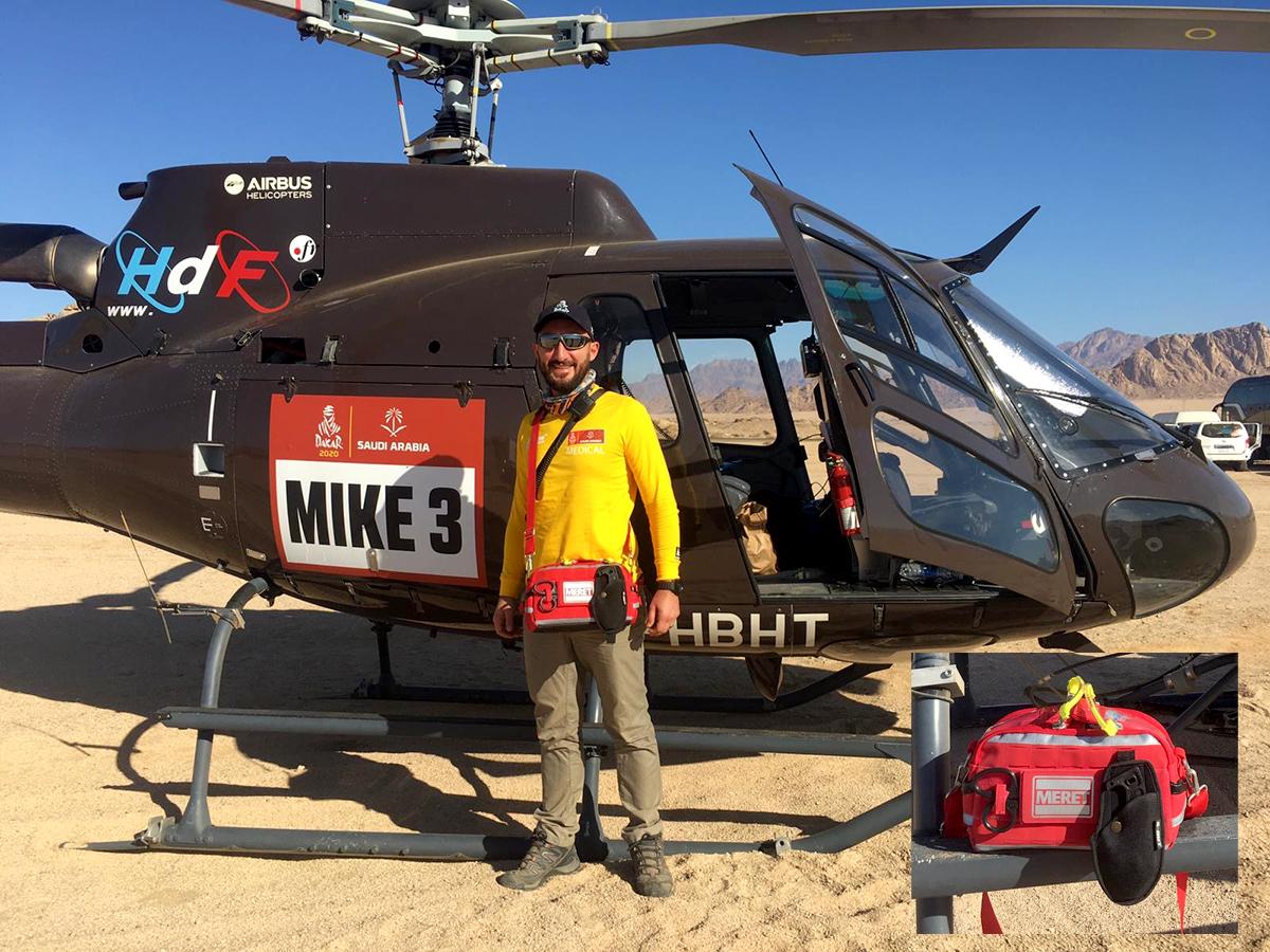 Bild som visar Dakarrallyts ansvarige läkare, Nicolas Fraimont. Han står framför en helikopter och bär en räddningsväska med en S-CUT i hölster.