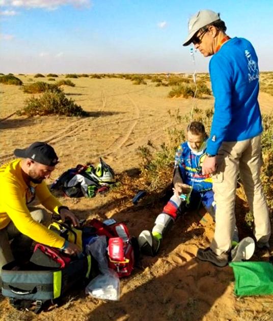 Bilden visar hur en deltagare som kraschat får första hjälpen av Dakarrallyts räddningsteam.